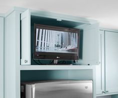 This TV is situated in a custom cabinet for easy viewing from the breakfast bar. It disappears behind flipper doors when not in use. Flatscreen TV from @lgusa