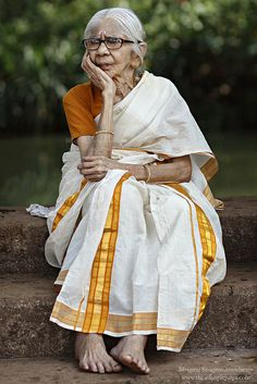 A Kerala woman sitting near the pond at Madhur Temple in Kasaragod.The women of Kerala typically wear authentic Kerala white sarees when visiting temples or attending any special ceromonies.