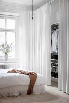 Gardinskena som fästs i taket. Draperiet fungerar som en smart och snygg lösning för att dölja klädförvaring i sovrum. För ett liknande uttryck rekommenderar vi Gotain skira linnegardiner, se hela sortimentet på www.gotain.com - Vi gör det enkelt att beställa skräddarsydda gardiner.