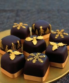 Chocolate covered individuals with gold hand piped snowflakes, trees and cut holly leaves, each finished with a gold ribbon