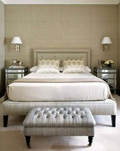 This bedroom is covered in upholstered panels of raw silk. It's the perfect way to add texture and warmth to a modern space. Combine with a beautifully upholstered headboard, classic sconces, and mirrored side tables for the epitome of hotel chic!  #homedecorideas #interiordesign #bedroom