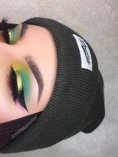 Green eye makeup, with bold black winged liner with a touch of gold glitter on the liner.