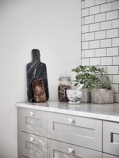 Grey kitchen with white marble counters and metro tiles