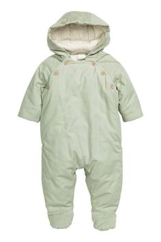 Padded corduroy all-in-one: BABY EXCLUSIVE/CONSCIOUS. Padded all-in-one suit in soft, narrow-wale corduroy made of organic cotton with a hood, buttons at the top and concealed press-studs at the sides. Concealed ribbing at the cuffs and full feet at the hems. Organic cotton jersey lining.