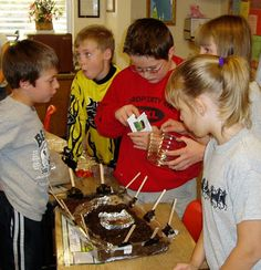 Five students cluster around their model biodome as one plants seeds in the soil.