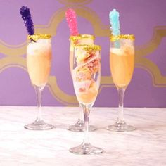 """Unicorn Mimosa Edible glitter Sherbet (flavor of your choice) Vodka Champagne Rock candy DIRECTIONS Dip a Champagne flute into water, and rim the glass with edible glitter. Add three scoops of sherbet. Add 1½ ounces of vodka to each Champagne flute. Top off with champagne. Garnish with rock candy (the """"horn"""")"""