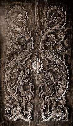 Antique wooden door, Sculpt a Dragon God. The age of approximately 200 years. In the ancient city of Songkla, Thailand. Photo by Noppharat
