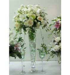 White Flowers in tall glass vase.... Could pop yours and your girls bouquets in vases like this and reuse it as an arrangement for reception