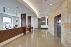 The main lobby's limestone wall continues into the second-floor lobby for the ophthalmology practice. Patients are greeted by the staff at a wood-clad reception desk. Photo: Patrick Y. Wong-Atelier Wong Photography