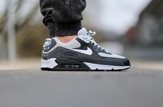This Nike Air Max 90 Essential uses a few different shaded of grey along with black and white on the upper that is constructed of suede, leather and mesh.