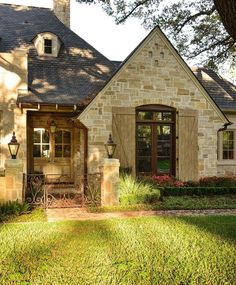 Provencal home with wood shutters and detailed wood front door