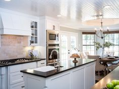 The+island+and+cabinets+are+painted+crisp+white+and+the+countertops+are+in+honed+black+granite.