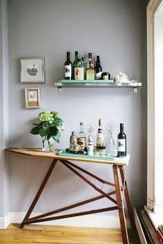 """9 Ways to Make All Your Clutter Look Gorgeous Without Throwing Anything Out: THINK BEYOND THE OLD BAR CART. """"Anything can be a bar,"""" says Soria—€""""this vintage ironing board is proof. Look around and see what you already have: a serving platter, a cutting board, or a single floating shelf. Just make sure there's enough room to actually make a drink!"""