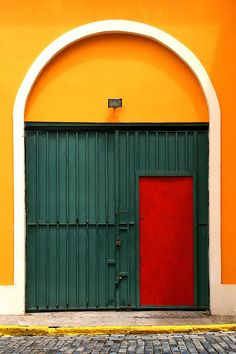 Red door within a green gate framed by a white arch on a yellow building. San Juan - Puerto Rico.