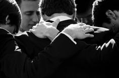 Young men who love God in a circle praying for an upcoming wedding and marriage.