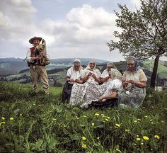 The lacemakers of Koniaków, a circle of village matrons at work in the mountains, with a view of the Beskid range in the background, and a ...