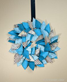 This wreath features a flock of  pretty papers, cut into leaf-like shapes, embossed with a whimsical print, and inked for interest. The shapes are stapled to a hand-cut cardboard ring that was covered  with coordinating paper, and the piece is hung from a length of ribbon.