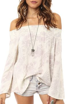 Softly colored botanical silhouettes sprawl over this free-spirited off-the-shoulder top with a flowing fit. Easy to pair with denim shorts and a necklace for a breezy summer ensemble.