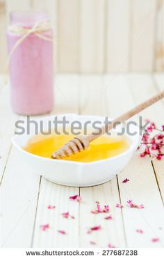 Yellow honey pot on rustic table with pink strawberry smoothie in the background - stock photo