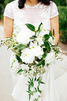 A wedding bouquet of garden roses, gardenias, clematis, olive branches, lily of the valley, seeded eucalyptus, and jasmine vines.