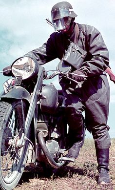 German motorcycle messenger wearing his rain gear. As anyone who has ever ridden on two wheels in the rain knows, the face mask becomes a true vision barrier in no time at all, unless one manages to do 50-60 mph, something that any such messenger wouldn't be able to achieve.