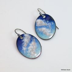 Inspired by sky watching, these blue and white copper enameled earrings dangle with clouds and sky. Artisan handmade and ready to mail, these are one of a kind and ready to mail.  Original art jewelry features vitreous enamels-glass enamels-kiln fired onto copper ovals. Created as earrings, each shape dangles from a handmade oxidized sterling silver ear wire. Skies have been a recurring motif in my work for many years, and I began to make enameled ones in 2014.  Each copper shape is almost 1…