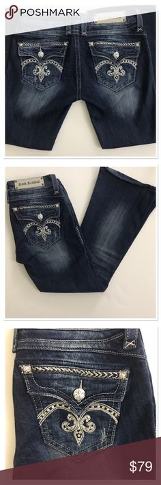 """Rock Revival Sasha Flare leg jeans Fleur de Lis 29 Rock Revival Sasha Flare leg jeans silver Fleur de Lis size 29. Featuring: logo patch on the back waist band Flare leg cut, fold flap button back pockets with Fleur de Lis silver buttons. Studded embroidered detail with crystals on the back pocket. Sanding, whispering, fading and distressed details. Gorgeous authentic jeans, new with no tags. Never been worn. Inseam 28"""" waist 15"""" Rock Revival Jeans Flare & Wide Leg"""