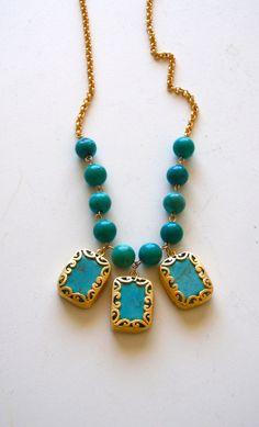 3 rectangular fretworked turquoises with 10 turquoise stones on a gold plated rolo chain