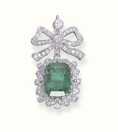 AN EMERALD AND DIAMOND PENDANT   Set with a rectangular-cut emerald in a circular and single-cut diamond frame suspended from a diamond-set ribbon bow top, mounted in 18k white gold