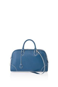 Oversized bowler style bag with contrast piping and paneling. Features elegant top handles as well as comfortable shoulder straps. Perfect carryall to take from day to night.100% Calf Leather.17