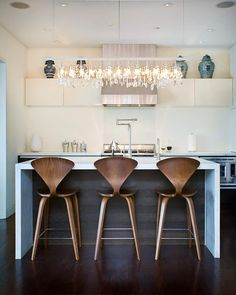 This striking contemporary kitchen features a sleek geometric design, with functional wooden stools, and a gorgeous modern crystal light fixture. By Marla Schrank Interiors.