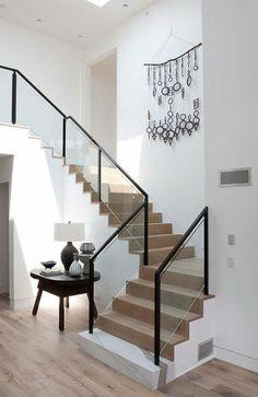 escalier flin en bois clair avec base blanche, garde corps en métal noir et verre blanc transparent, petite table carrée noire avec lampadaire avec abat jour blanc, murs tout blancs