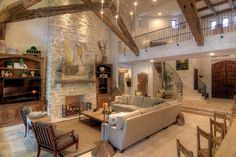 casual mediterranean living room with wood beam ceilings and loft