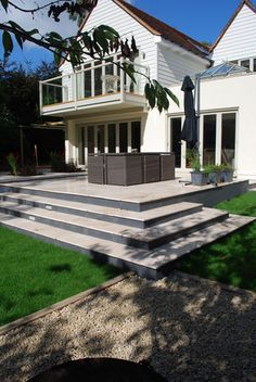 Sleek limestone terrace with inset rill and planting areas.