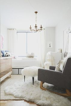 Chic boy's nursery features a two tone crib next to a twin guest bed facing a lacquered dresser and changing table.