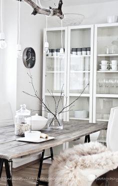 Artefacto de iluminación muy original. Mesa rústica de madera con caballetes y mucho blanco.