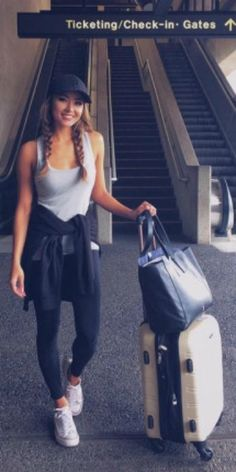 Jessica Ricks + simple grey vest + black leggings + matching black cap + white Converse sneakers + comfortable travel style   Brands not specified.