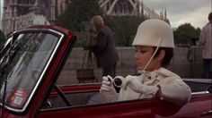 """Audrey Hepburn, Driving Red Autobianchi Bianchina Special Cabriolet, Givenchy White Hat, """"How to Steal a Million"""" (1966)  Screen capture of 1966 romantic comedy, """"How to Steal a Million,"""" starring Belgium-born British actress Audrey Hepburn (May 4, 1929 - January 20, 1993), London-born actor Peter O'Toole (August 2, 1932 - December 14, 2013), and Oscar-winning Welsh actor Hugh Griffith (May 30, 1912 - May 14, 1980)."""