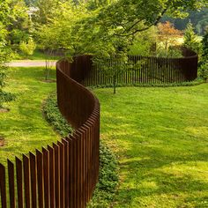 Coolest fence I have ever seen, Corten steel verticals with concrete footing hidden by ground cover""