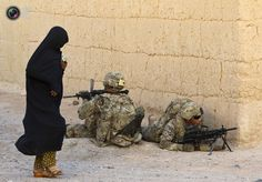 Coolest Pix Of 2012 Week 23. A woman walks past U.S. Army soldiers of 82nd Airborne Division securing an area during a patrol in the town of Senjaray, Zahri district of Kandahar province, southern Afghanistan. SHAMIL ZHUMATOV/REUTERS