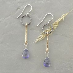 Beautiful, handcrafted dangling iolite earrings featuring faceted drops of iolite swaying from hammered 14kt gold fill bars and an oxidized sterling silver hoop.