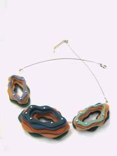 Gris Blue polymer clay jewelry. I love the riveted layers!