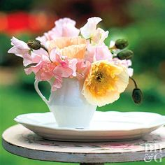 A white creamer is a perfectly elegant alternative to a regular vase. Fill it with pink sweet peas and yellow poppies. Want poppies to last longer? Cut them from the plant just as they begin to open. Sear the stems with a flame and immediately place in lukewarm water.