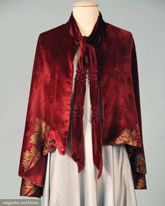 Burgundy silk velvet, cape bottom w/ metallic gold stencilled leaf design, possibly Gallenga or Fortuny fabric, neck collar band extends into front tie sash.  augusta-auction.com