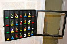 Lego Minifigure display case made from a shot glass shadow box and hot glued lego blocks.