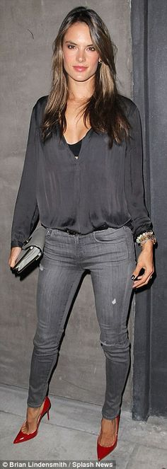 Alessandra rocks a silky top, grey skinny jeans and eye-catching red heels