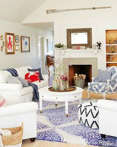 Casual elegant coastal nautical living room with fun accents. Sea life octopus and jelly fish art and a wall mounted oar high on the ceiling above the fireplace. Featured on CC:  http://www.completely-coastal.com/2015/10/small-coastal-beach-theme-living-room-ideas.html