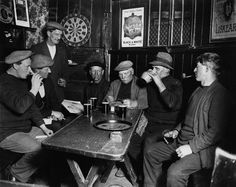1932: A group of men, one knitting, others raising glasses of beer, at the Jolly Sailor's Inn. Cornwall, England. E.O. Hoppé/CORBIS