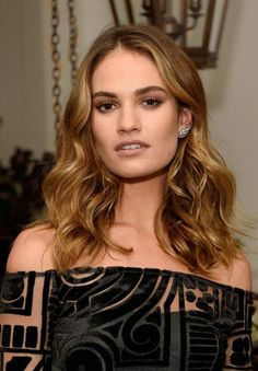 Lily James looked her usual gorgeous and fashionable self as she stepped out in a charcoal hued dress with black abstract print all over and an off shoulder neckline that showed off her sculpted shoulders and teased a hint of her cleavage with sheer overlay, while posing for the cameras at the event held to celebrate the launch of My Burberry Black on Monday night (August 22) in London, England.