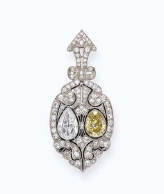 A BELLE EPOQUE COLORED DIAMOND BROOCH -  Centering upon a pear-shaped yellow diamond and diamond, set within an old European and single-cut diamond openwork pierced plaque, enhanced by ribbon motifs, with a black onyx backing, mounted in platinum, circa 1910
